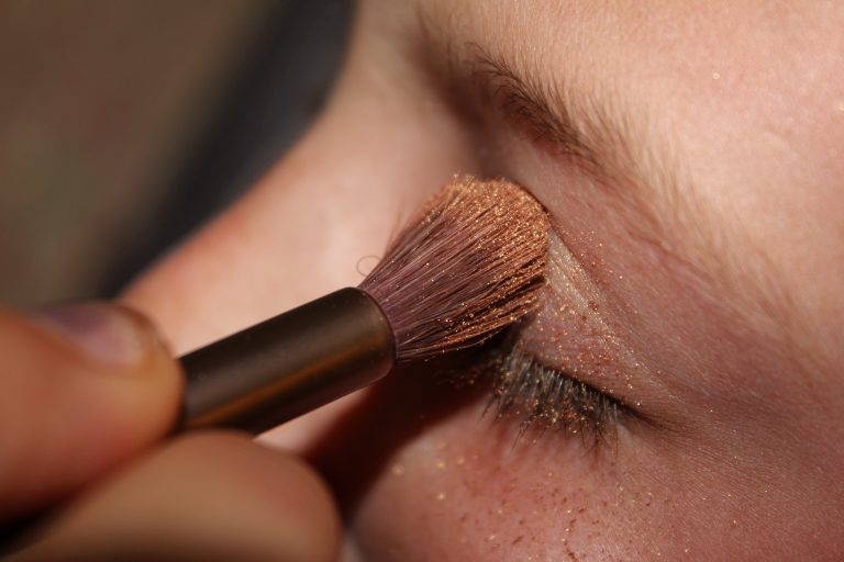 woman applying brown glittered eyeshadow
